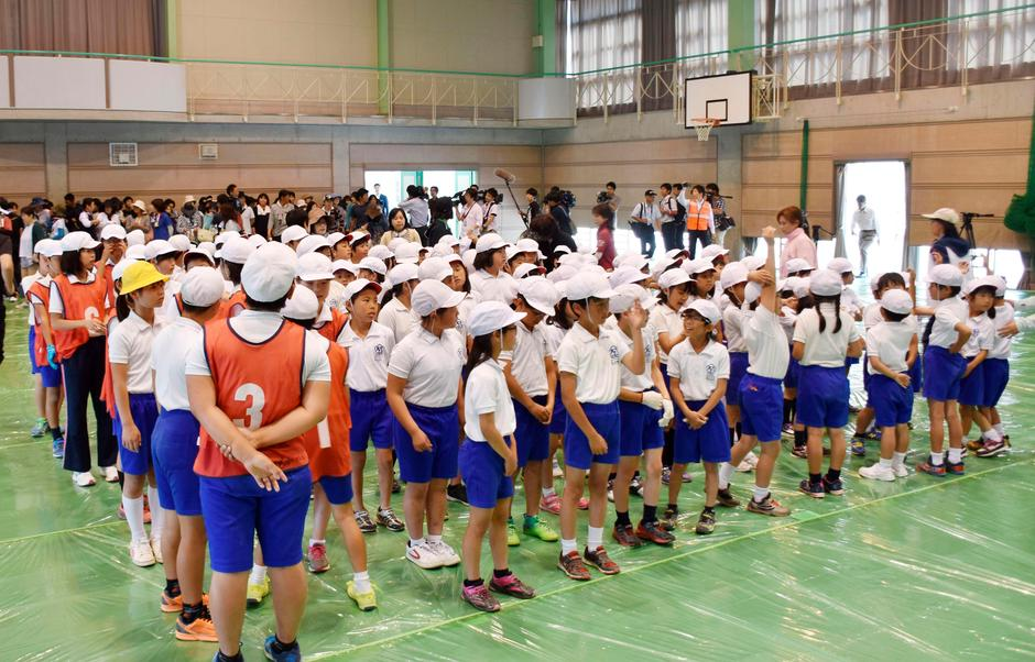 Elementary school students take part in an evacuation drill for a simulated North Korean missile attack, in Abu, Yamaguchi prefecture, Japan in this photo ...