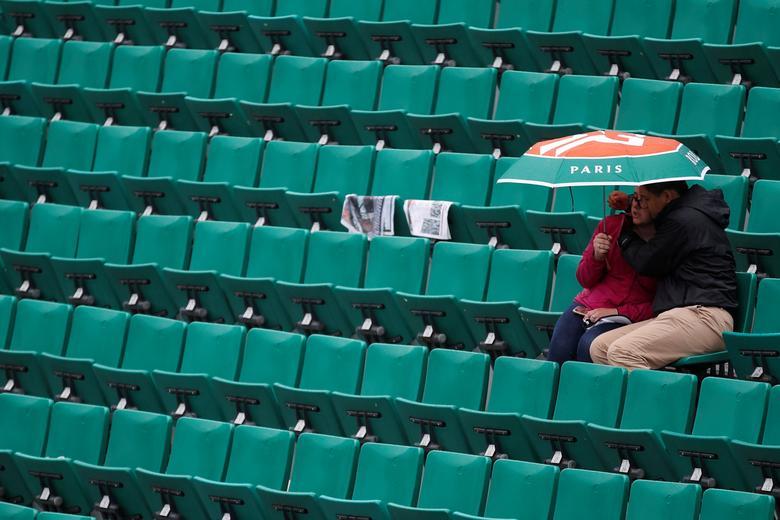 Tennis - French Open - Roland Garros, Paris, France - June 3, 2017 A fan with a umbrella during a rain delay Reuters / Christian Hartmann