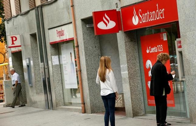 People use a Santander's cash dispenser (ATM) as a man leaves a Banco Popular office in Barcelona, Spain June 7, 2017. REUTERS/Albert Gea