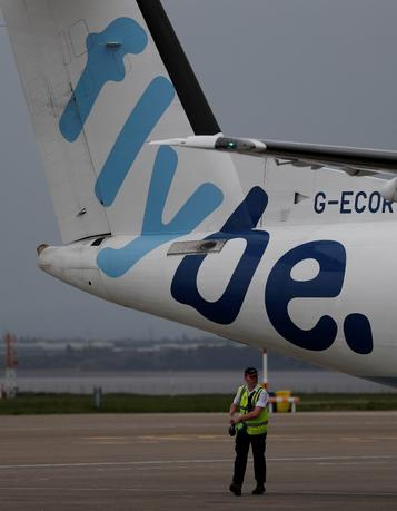 FILE PHOTO: An airport worker examines a Flybe aircraft before it takes off from Liverpool John Lennon Airport in northern England, May 19 , 2016. REUTERS/Phil Noble/File Photo