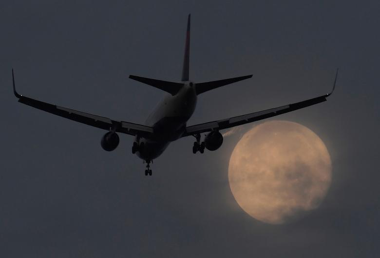 FILE PHOTO: A passenger aircraft makes it's landing approach to Heathrow airport in front of a ''super moon'' at dawn in west London, Britain, October 17, 2016.  REUTERS/Toby Melville