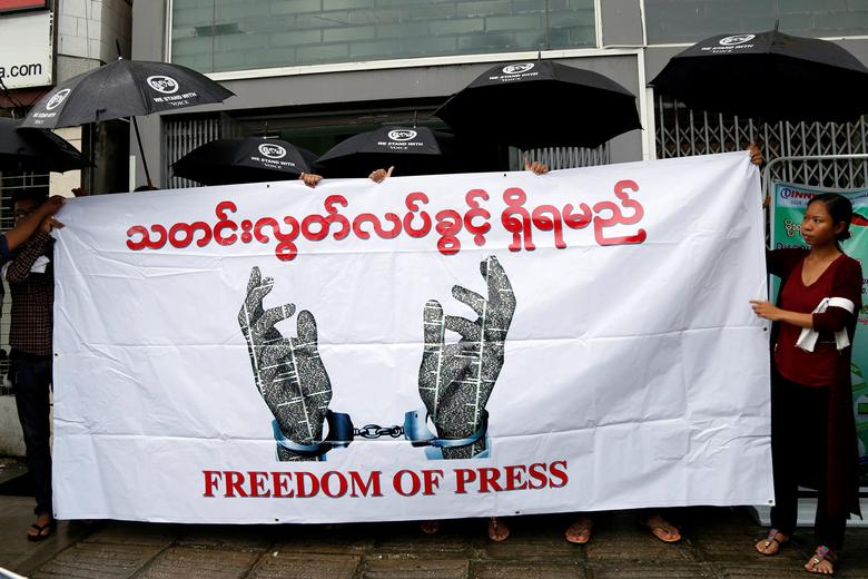 Journalists hold a banner as they protest against a law they say curbs free speech, at the start of a trial of two journalists who the army is suing for defamation over a satirical article, in Yangon, Myanmar June 8, 2017. REUTERS/Stringer NO SALES NO ARCHIVES EDITORIAL USE ONLY