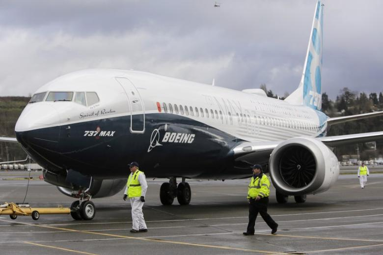 FILE PHOTO: Ground crew members escort a Boeing 737 MAX as it returns from a flight test at Boeing Field in Seattle, Washington January 29, 2016.  REUTERS/Jason Redmond/File Photo
