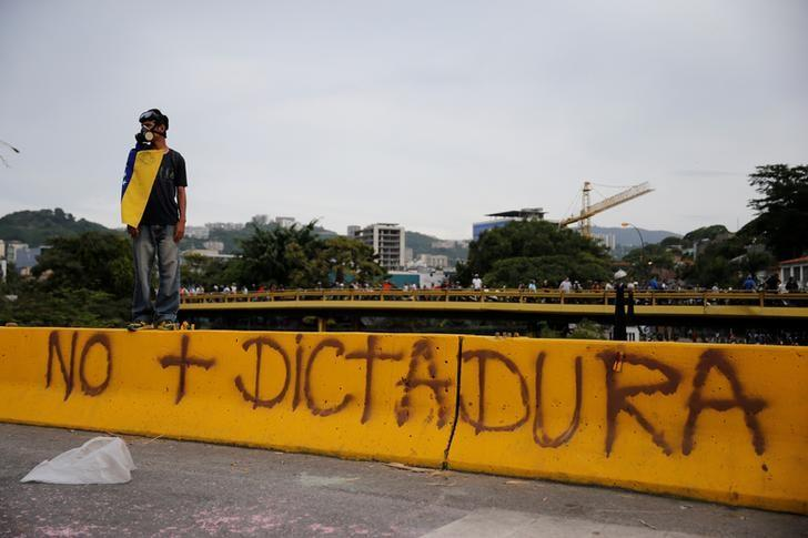 Demonstrator stands next to a sign reads 'No more dictatorship' at a rally against Venezuelan President Nicolas Maduro's government in Caracas, Venezuela, June 9, 2017. REUTERS/Ivan Alvarado/Files