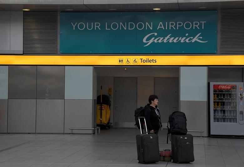 FILE PHOTO: A passenger waits outside of Gatwick Airport in southern England, Britain, October 9, 2016. Support services company Mitie has had a contract to work with Gatwick for a number of years. REUTERS/Toby Melville/File Photo