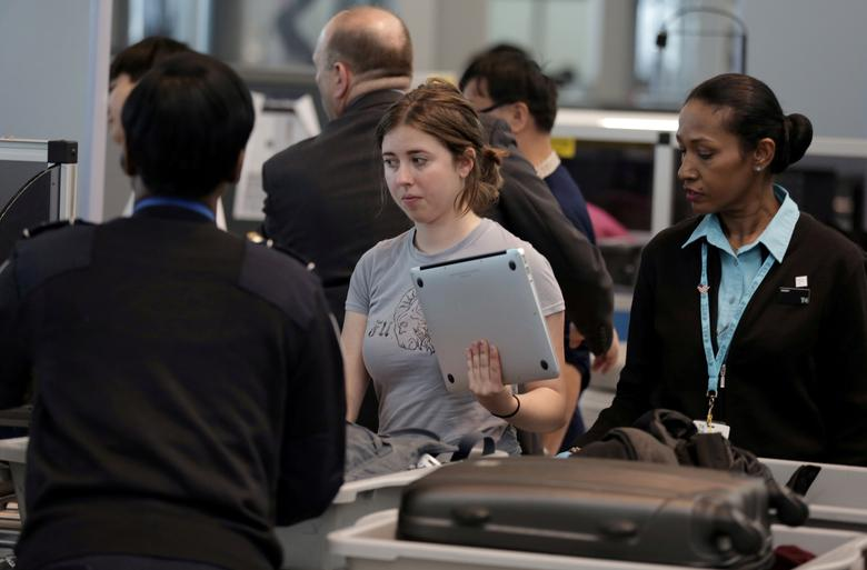 FILE PHOTO: A traveler takes her laptop out of her bag for scanning at Terminal 4 of JFK airport in New York City, U.S., May 17, 2017. REUTERS/Joe Penney/File Photo