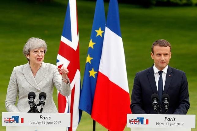 6月13日、メイ英首相(写真左)とマクロン仏大統領(右)は、パリで首脳会談を行い、テロ対策で連携を強化することで一致、インターネット上に掲載されるヘイトスピーチ(憎悪表現)の取り締まりを企業に促す取り組みで協力する方針を示した(2017年 ロイター/Philippe Wojazer)