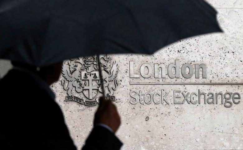 FILE PHOTO: A man shelters under an umbrella as he walks past the London Stock Exchange in London, Britain August 24, 2015. REUTERS/Suzanne Plunkett/File Photo
