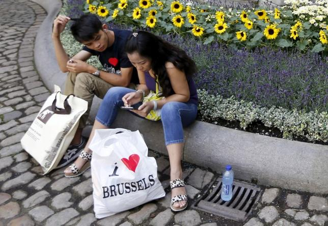 FILE PHOTO: Tourists take a break in the decorated yard of Brussels' town hall, Belgium, August 12, 2015.    REUTERS/Francois Lenoir/File Photo