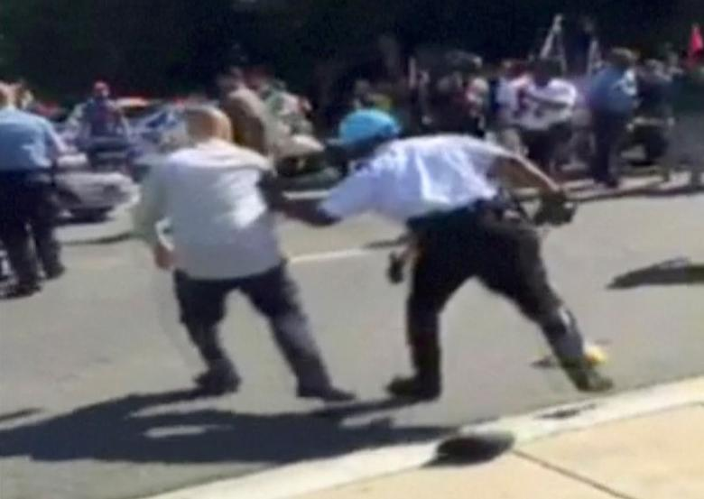 FILE PHOTO: A Police officer pushes a man away from protesters, in this still image captured from a video footage, during a violent clash outside the Turkish ambassador's residence between protesters and Turkish security personnel during Turkish President Tayyip Erdogan's visit to Washington, DC, U.S. on May 16, 2017.   Courtesy Armenian National Committee of America/Handout via  REUTERS