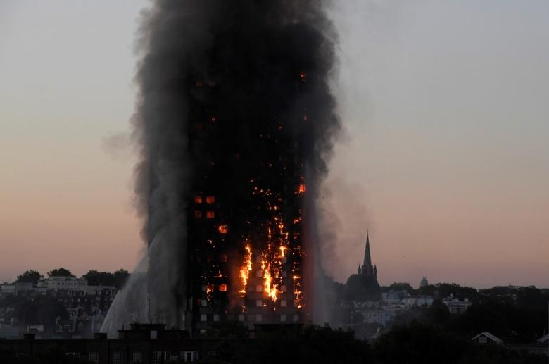 Flames and smoke billow as firefighters deal with a serious fire in the Grenfell Tower apartment block at Latimer Road in West London. REUTERS/Toby Melville