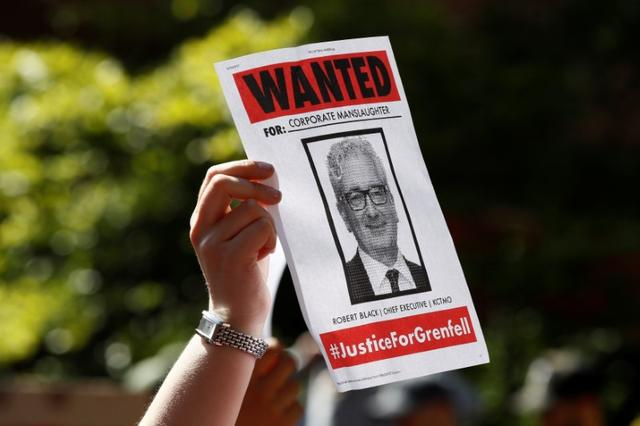 A demonstrator holds a wanted poster during a protest at Kensington Town Hall, following the fire that destroyed The Grenfell Tower block, in north Kensington, West London, Britain June 16, 2017. REUTERS/Stefan Wermuth