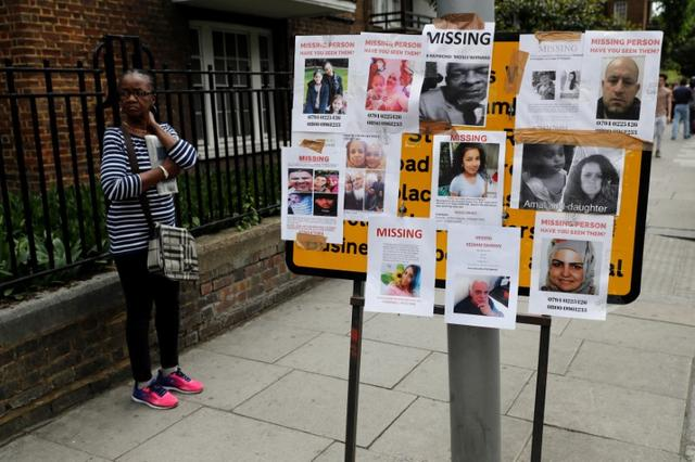 A woman stands by missing person posters near The Grenfell Tower block, destroyed by fire, in north Kensington, West London, Britain June 16, 2017. REUTERS/Stefan Wermuth