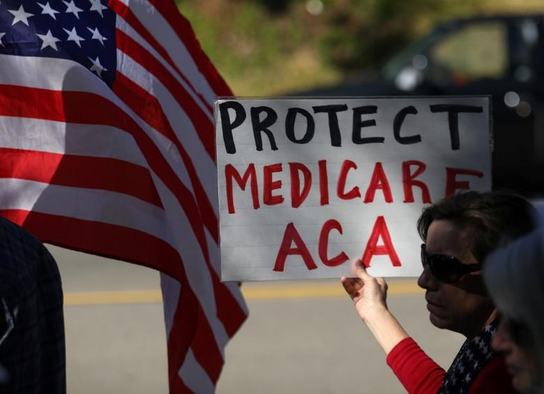 FILE PHOTO: Demonstrators protest over the repeal and replacement of Obamacare outside the offices of Republican congressman Darryl Issa in Vista, California, U.S., March 7, 2017.    REUTERS/Mike Blake
