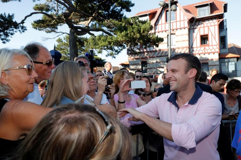 French President Emmanuel Macron shakes hands with people as he leaves his home in Le Touquet, France June 17, 2017. REUTERS/Philippe Wojazer