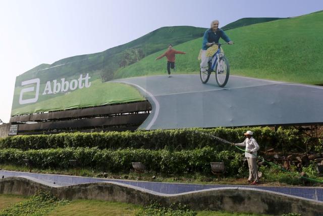 FILE PHOTO: A worker waters plants next to an advertisement billboard of Abbott in Mumbai, India, November 12, 2015. REUTERS/Danish Siddiqui/File photo