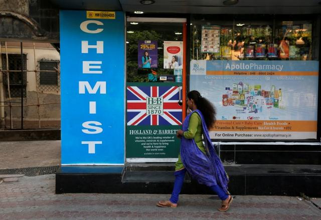FILE PHOTO: A woman walks past a chemist shop in Mumbai, India April 28, 2017. REUTERS/Shailesh Andrade/File Photo