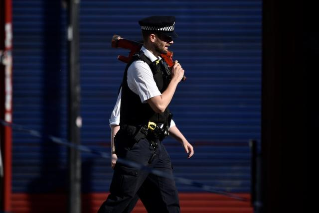 Police officers walk behind cordon tape at the scene of an attack where a man drove a van at Muslim worshippers outside a mosque in Finsbury Park in North London, Britain, June 19, 2017. REUTERS/Hannah McKay