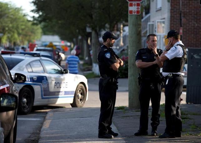 6月21日、米連邦捜査局(FBI)は、ミシガン州フリントのビショップ国際空港ターミナル内で1人の警官が刃物で刺された事件を「テロ行為」として捜査していると発表した。写真は容疑者の自宅周辺で話す警察の捜査員。加モントリオールで撮影(2017年 ロイター/Christinne Muschi)