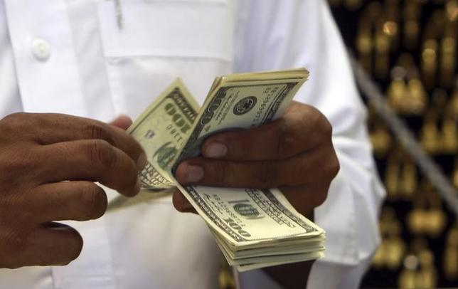 6月27日、自国通貨の支援能力の指標であるサウジアラビア中銀の対外純資産(NFA)は、今年も大幅な減少が見込まれている。写真は米ドル紙幣。同国メッカで2012年10月撮影(2017年 ロイター/Amr Abdallah Dalsh)