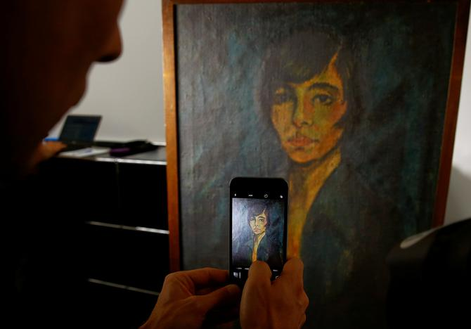 A man uses his mobile phone as he takes a picture of the painting 'Maschka' by late German artist Otto Mueller during a news conference, after the arrival of the first artworks from the Dossier Gurlitt, at the Kunstmuseum Bern art museum in Bern, Switzerland July 7, 2017. Arnd Wiegmann