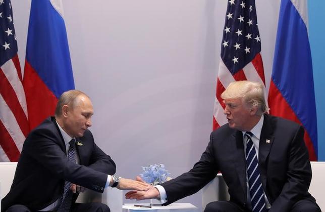 7月10日、ロシアのペスコフ大統領報道官は米ロ首脳がサイバー安全保障対策の共同組織創設について協議したと確認。ただ、相互に確約した事項はないという。写真はトランプ大統領(右)とプーチン大統領(左)。7日、ハンブルクで撮影(2017年 ロイター/Carlos Barria)