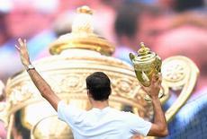 روجر فيدرر يحمل كأس بطولة ويمبلدون للتنس في لندن يوم الأحد. تصوير: توبي ملفيل - رويترز