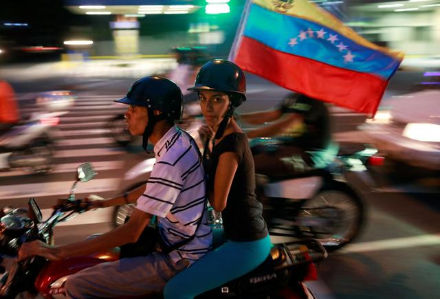 Opposition supporters ride on a motorcycle after an unofficial plebiscite against President Nicolas Maduro's government and his plan to rewrite the constitution, in Caracas, Venezuela July 16, 2017. REUTERS/Marco Bello