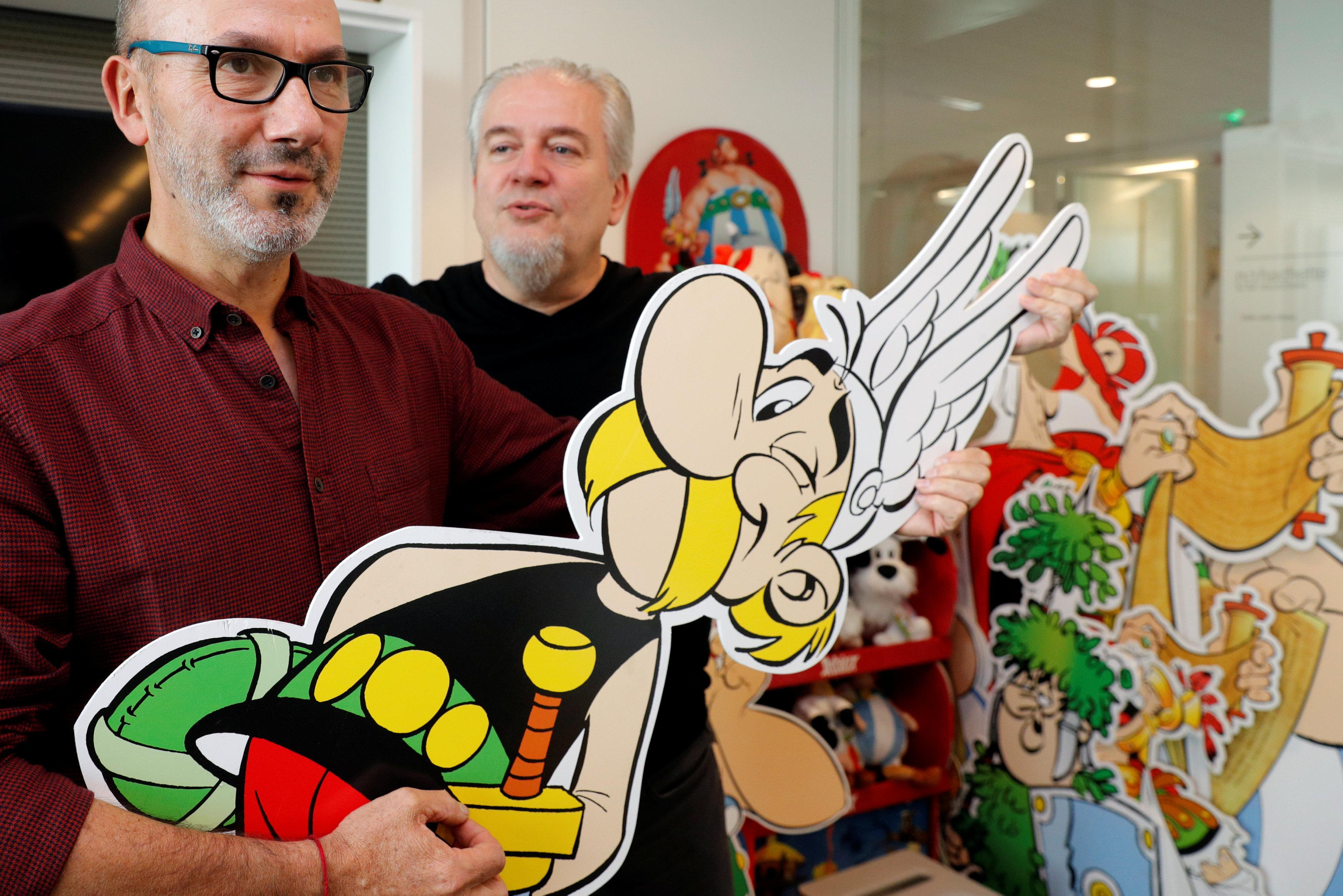 Author Jean-Yves Ferri (L) and illustrator Didier Conrad (R) pose holding a cardboard cut-out of Asterix during an interview for their new comic album