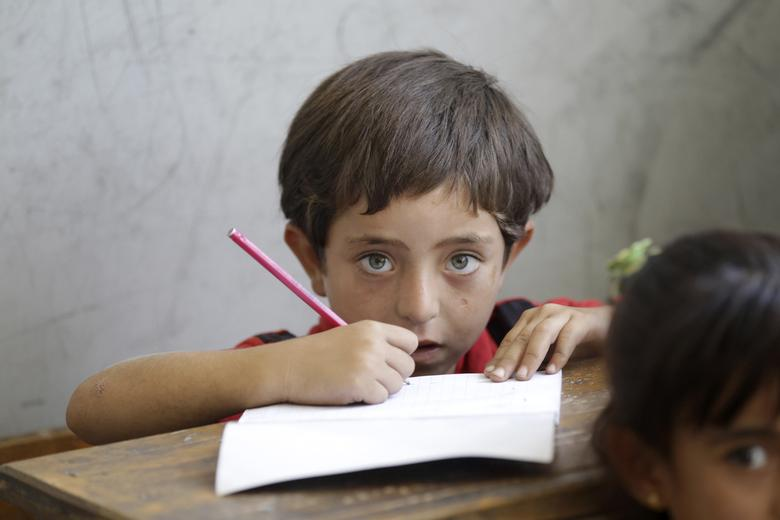 A boy looks on as he attends a class in a school in southern countryside of Idlib, Syria. September 2015. REUTERS/Khalil Ashawi