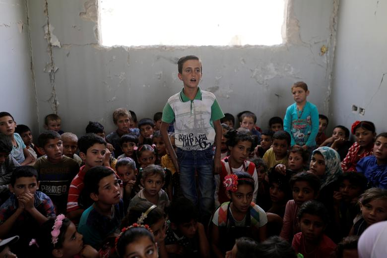 Pupils sit together in a shared classroom at a damaged school in al-Saflaniyeh in eastern Aleppo's countryside, Syria. September 2017. REUTERS/Khalil Ashawi