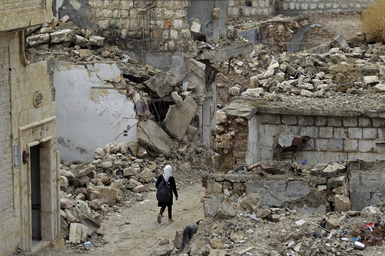 A school girl walks past damaged buildings in the rebel-controlled area of Maaret al-Numan town in Idlib province, Syria. October 2015. REUTERS/Khalil Ashawi