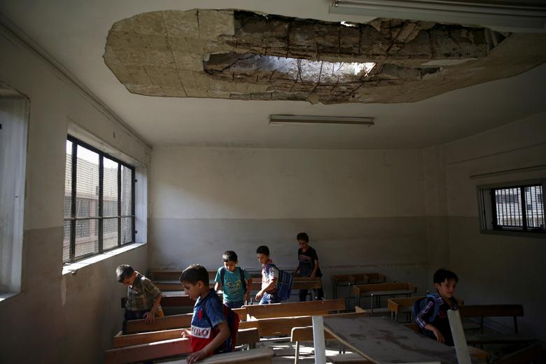 Students walk in a damaged classroom on the first day of school in the rebel-held Douma neighbourhood of Damascus, Syria. September 2017. REUTERS/Bassam Khabieh