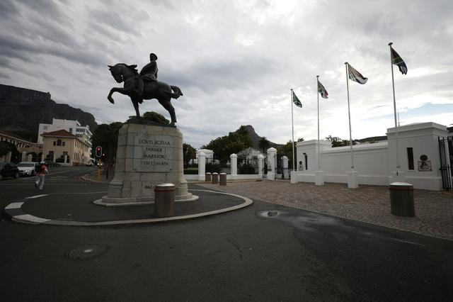 Flags fly behind the statue of Louis Botha, South Africa's first Prime Minister, outside Parliament in Cape Town, South Africa, February 13, 2018.  REUTERS/Mike Hutchings