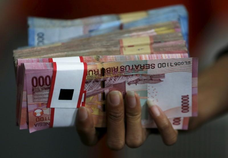 An Employee Of A Money Changer Holds Stack Indonesia Rupiah Notes Before Giving It To Customer In Jakarta October 8 2017 Reuters Beawiharta