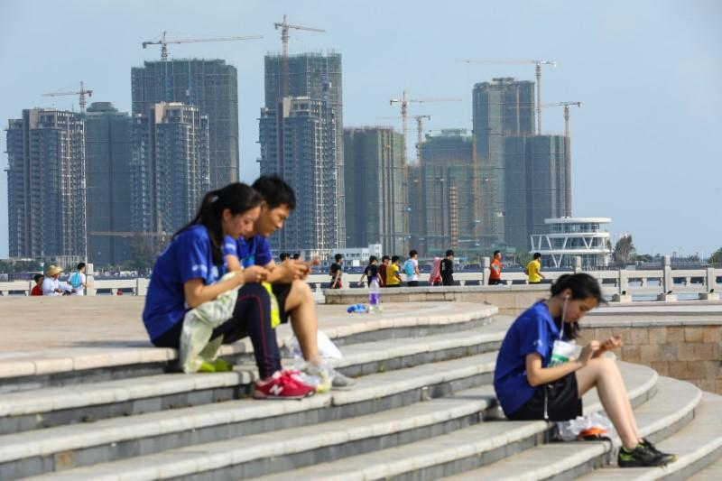 People sit on steps against a backdrop of residential buildings under construction, in Haikou, Hainan province, China April 22, 2018. Picture taken April 22, 2018.  Stringer