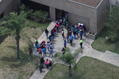 Migrant children make their way inside a building at Casa Presidente, an...