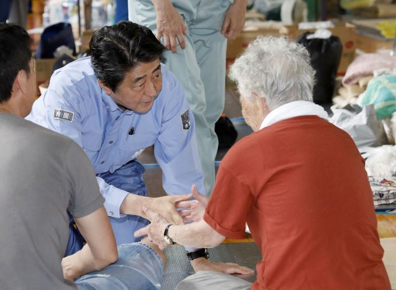 Japan's Prime Minister Shinzo Abe meets local residents staying at an evacuation center in Kurashiki, Okayama Prefecture, Japan, in this photo taken by Kyodo July 11, 2018. Mandatory credit Kyodo/via
