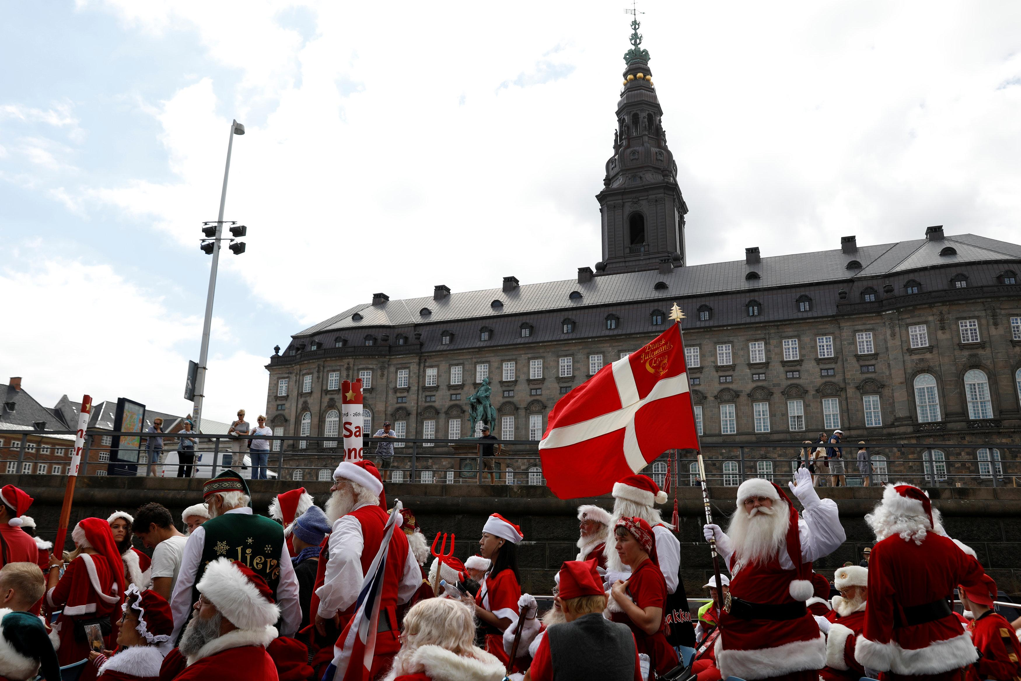 People dressed as Santa Claus arrive outside Christiansborg Palace as they take part in the World Santa Claus Congress, an annual event held every summer in Copenhagen, Denmark, July 23, 2018.  Andrew Kelly