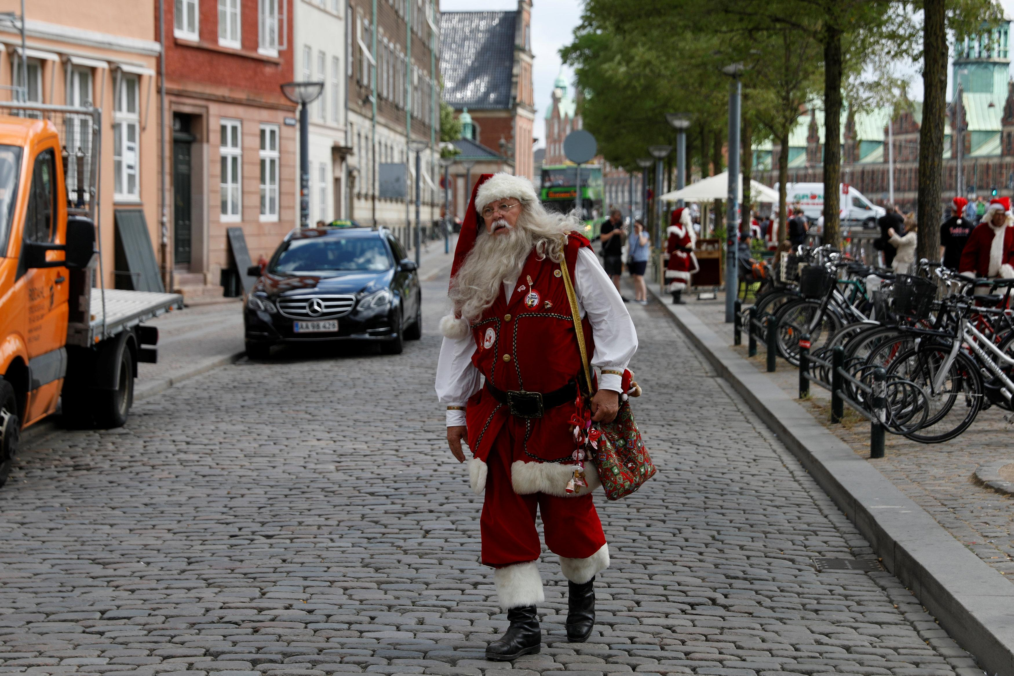 A man dressed as Santa Claus walks through the streets between events for the World Santa Claus Congress, an annual event held every summer in Copenhagen, Denmark, July 23, 2018.  Andrew Kelly