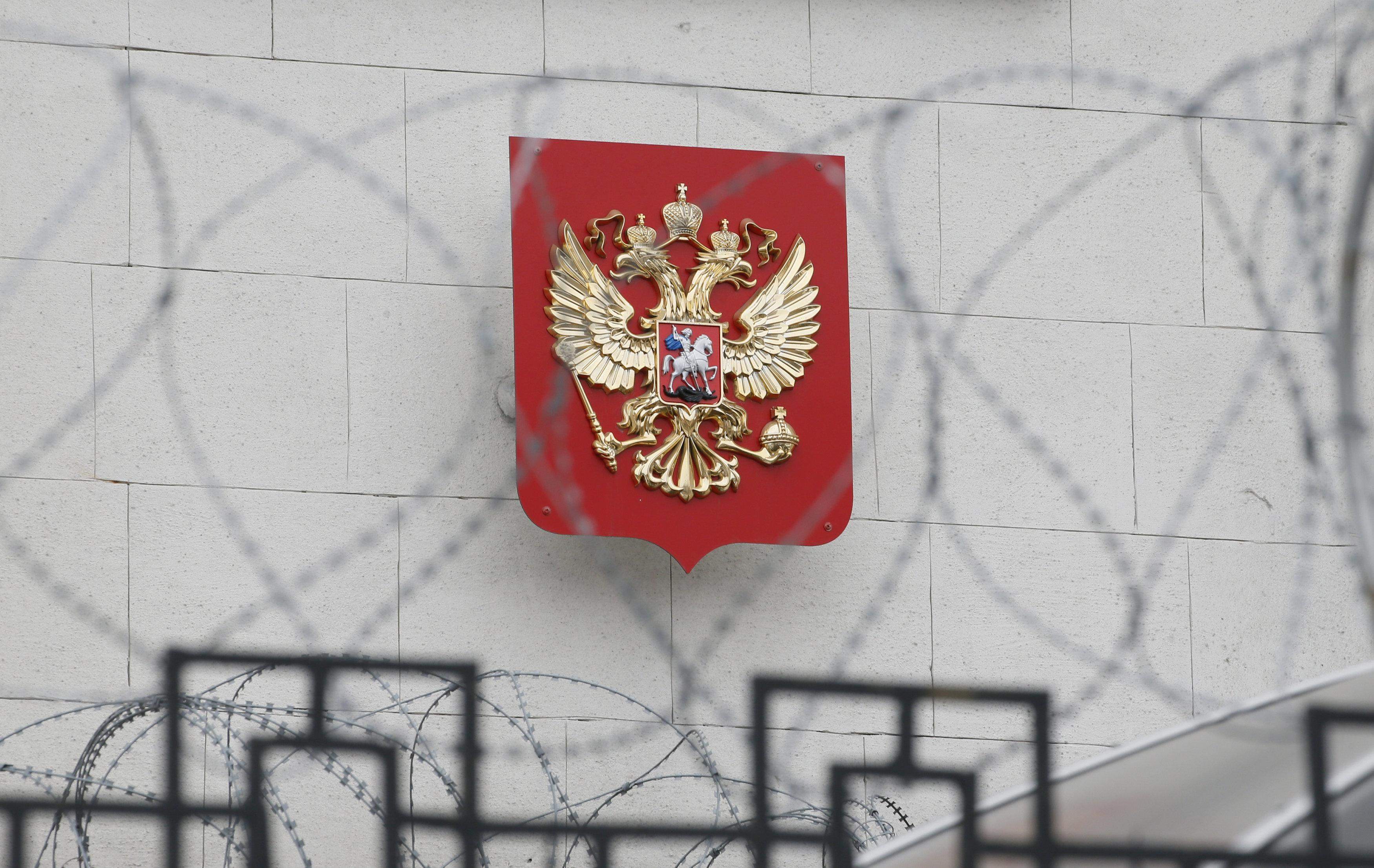 A coat of arms is seen through barbed wire on the wall of the Russian embassy in Kiev, Ukraine March 26, 2018. Gleb Garanich