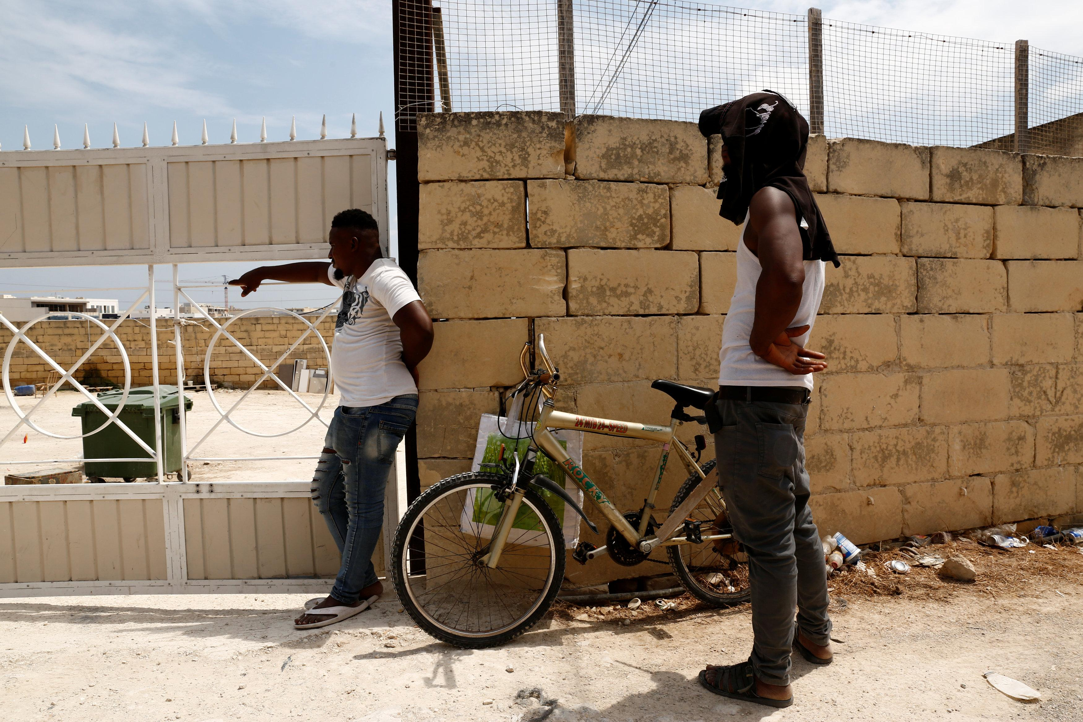 Evicted migrants stand outside a farm where police evicted some 110 African migrants who had been living in stalls formerly used by cows, in Qormi, Malta August 13, 2018.  Darrin Zammit Lupi