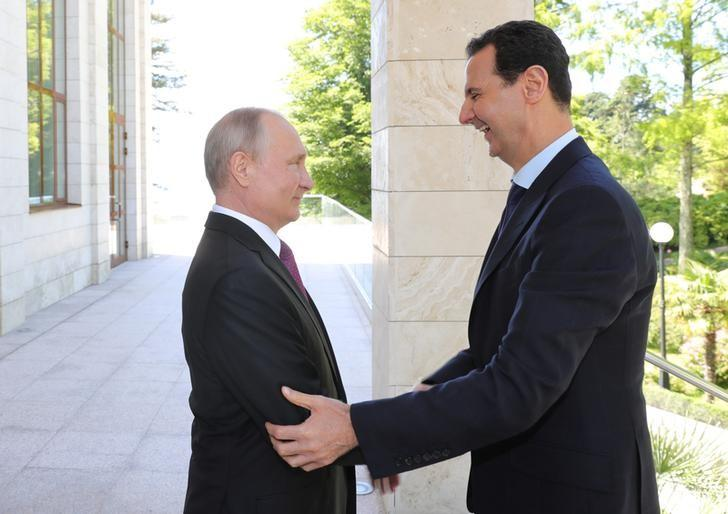 Russian President Vladimir Putin welcomes Syrian President Bashar al-Assad during their meeting in the Black Sea resort of Sochi, Russia May 17, 2018. Sputnik/Mikhail Klimentyev/Kremlin via