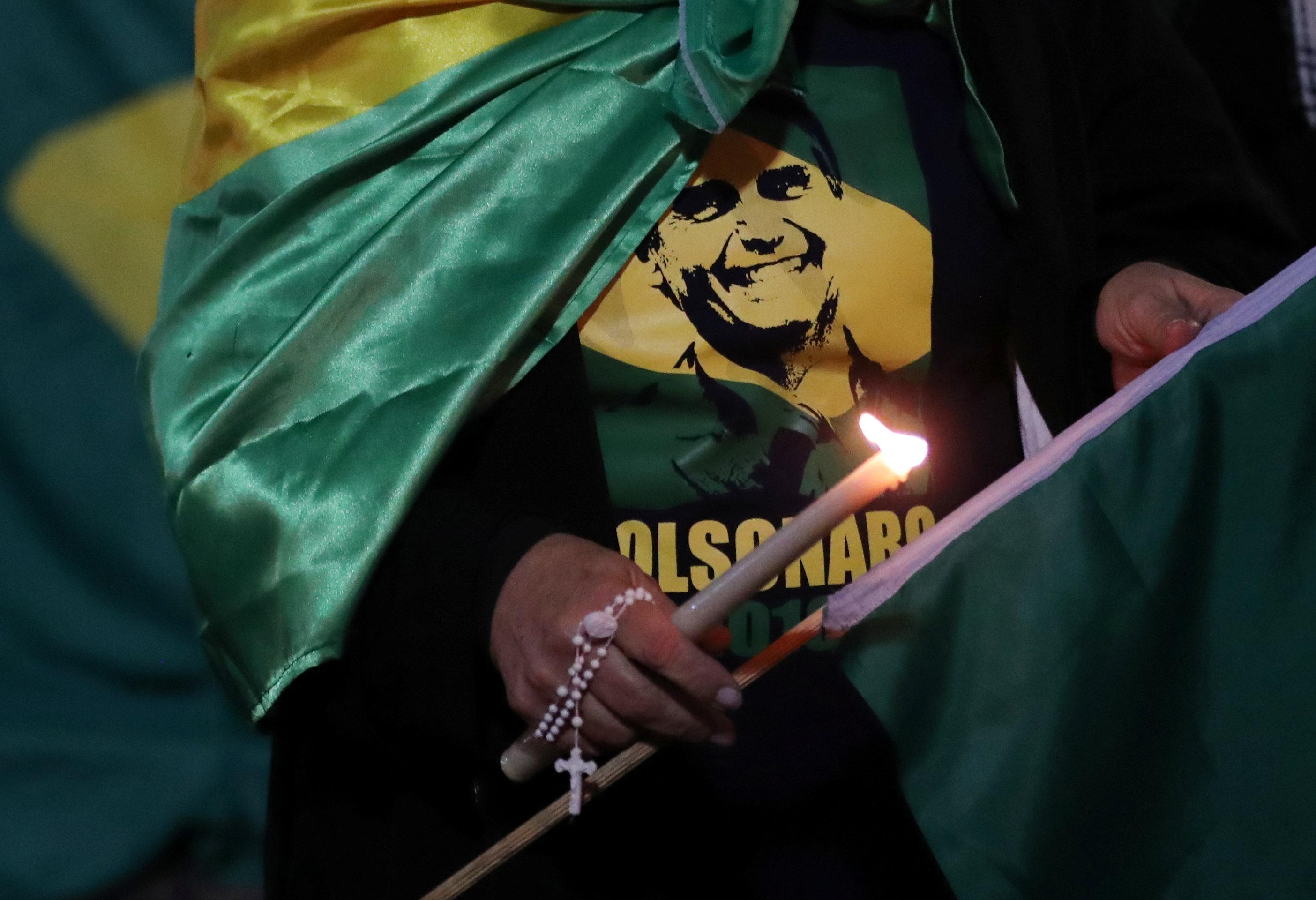 A woman lights a candle for presidential candidate Jair Bolsonaro after he was stabbed by a man in Juiz de Fora at Paulista avenue in Sao Paulo, Brazil September 6, 2018. Paulo Whitaker