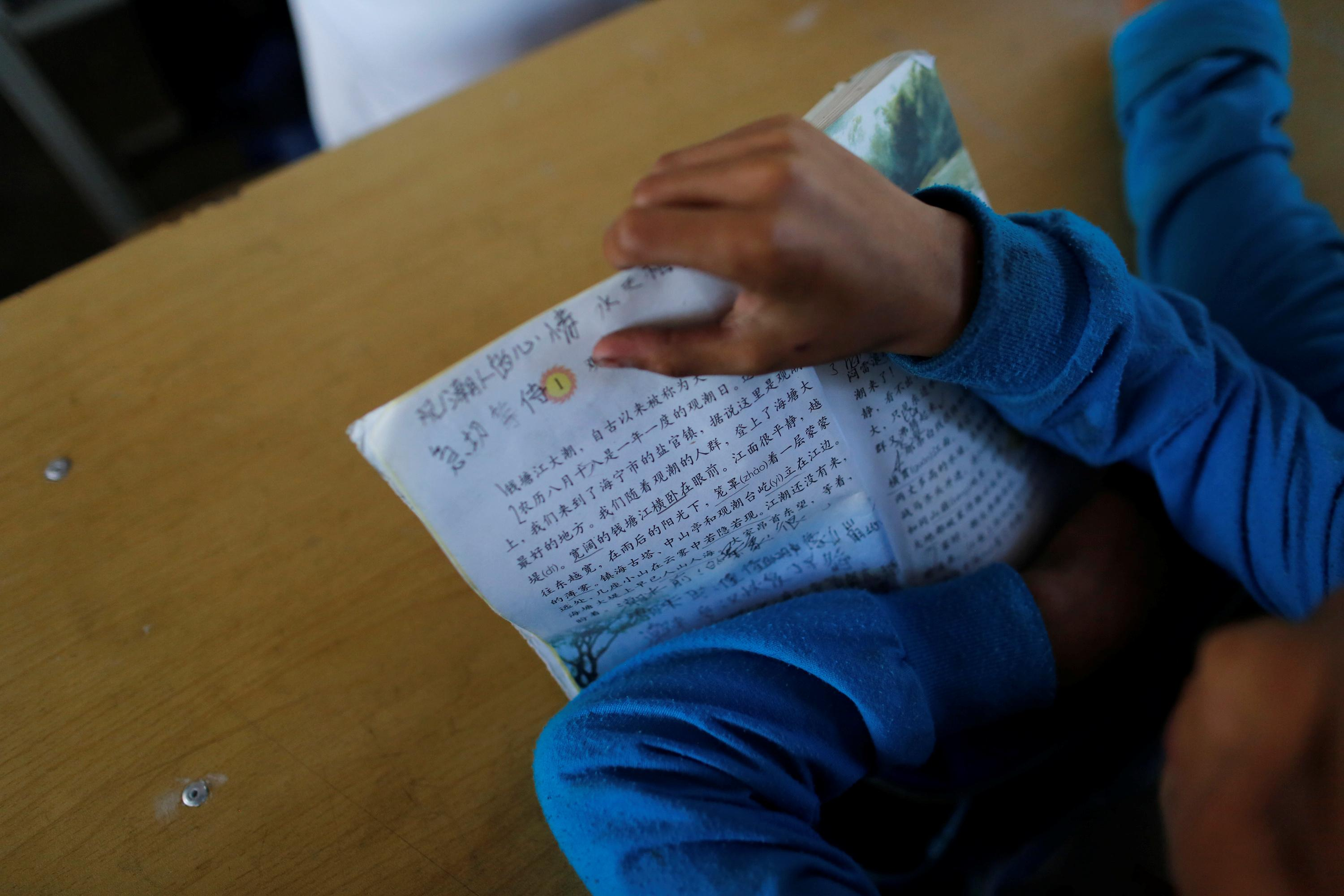 A child holds a book during a Chinese language lesson in a school at Namtit, Wa territory in northeast Myanmar November 30, 2016. Soe Zeya Tun