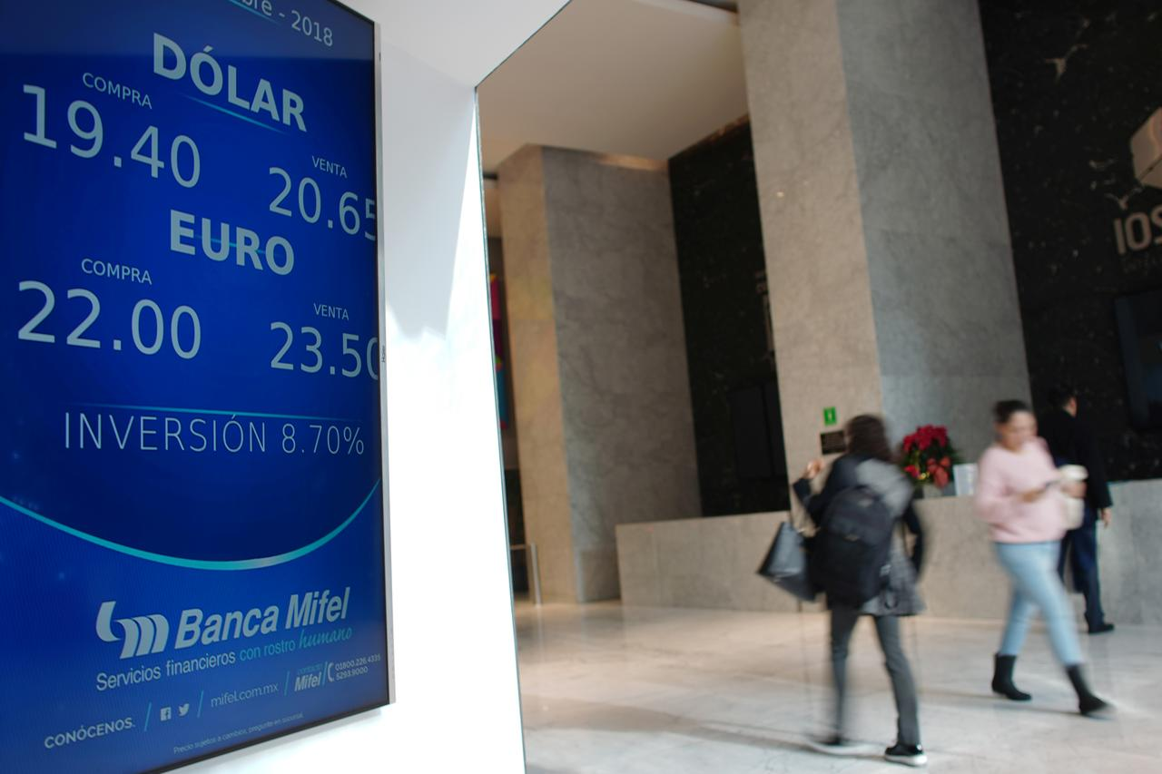 People Walk Past A Board Displaying The Exchange Rates Of Mexican Peso Against U S Dollar And Euro At Bank In Mexico City December 17 2018