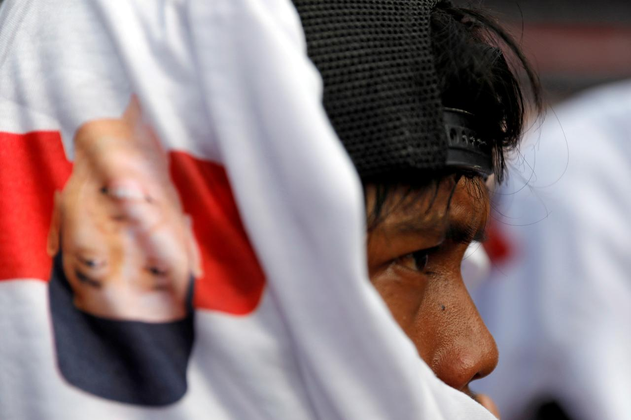 A supporter covers his head with a t shirt with the image of indonesias incumbent presidential candidate joko widodo during a campaign rally at gelora bung