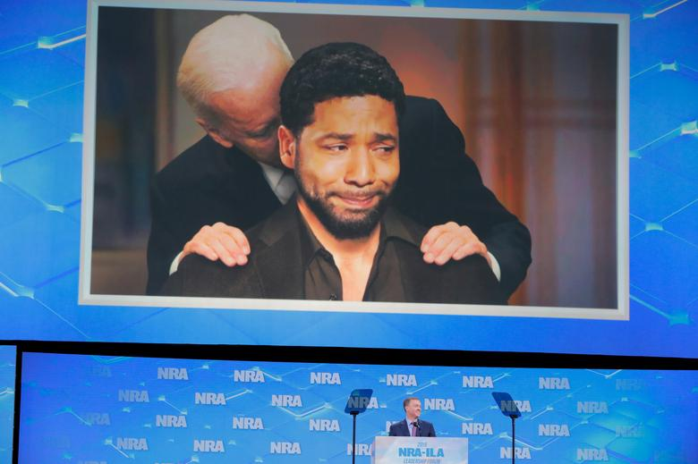 A composite meme of former Vice President Joe Biden and Jussie Smollett is on display while Chris Cox speaks. REUTERS/Lucas Jackson