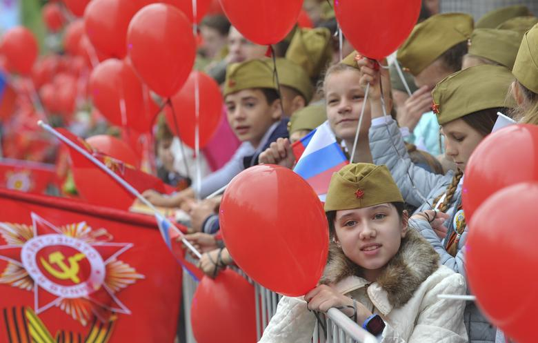 Children watch the Victory Day parade in Rostov-on-Don, Russia. REUTERS/Sergey Pivovarov