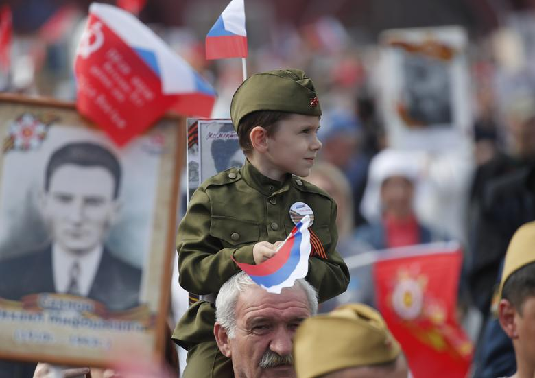 People take part in the Immortal Regiment march during celebrations of the Victory Day in Red Square in central Moscow, Russia. REUTERS/Maxim Shemetov